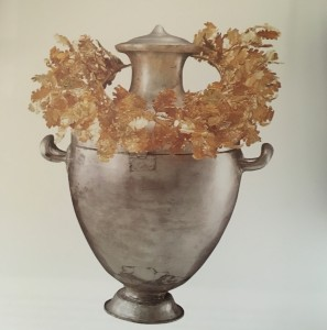A gold wreath of oak leaves on a silver funerary urn